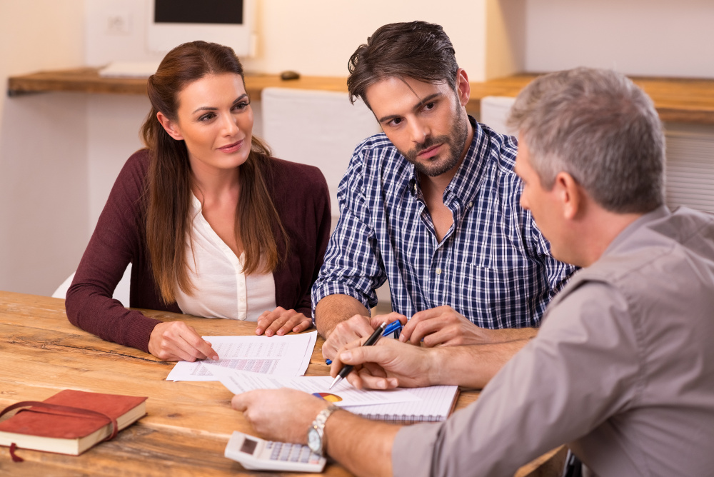 Businessman explaining loan policy to young couple. Happy young couple discussing with a financial agent their new investment. Financial consultant presents bank investments to a young couple.